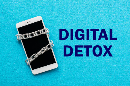 White smartphone with metal chain on blue background. Digital detox, dependency on tech, no gadget and devices concept Banco de Imagens