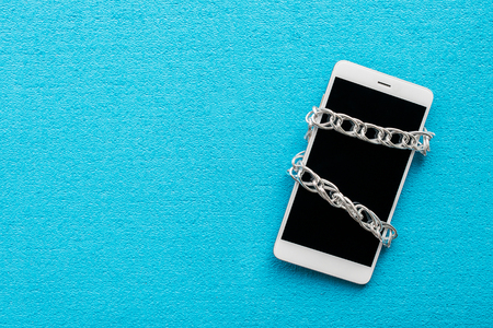 White smartphone with metal chain on blue background. Digital detox, dependency on tech, no gadget and devices concept 免版税图像