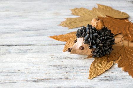 Autumn crafts. Children's fall crafts and creativity, Hedgehog made from modeling clay, sunflower seeds and nuts, on dry yellow leaves. Ideas for children's art