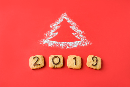 Flour Silhouette Christmas Tree with cookies digits 2019 on red background. Delicious bakery sweet confectionery Christmas card. Idea of merry new year xmas 2019 holiday