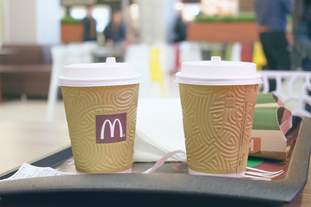 CHERKASY, UKRAINE  – 14 October, 2018:  Two Cup of McDonalds coffee in the background of the McDonalds restaurant. McDonalds fast food with bill, check.