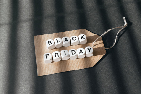 Sale banner with text word Black Friday on cardboard label on dark background. Black Friday sale concept