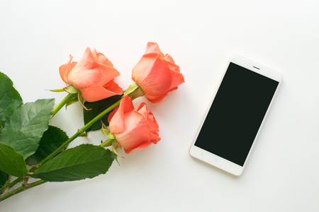 Top view of mobile phone with copy space and roses on white background. flat lay, mock up. Woman's workplace with phone and flowers.