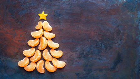 Tangerine christmas tree  on dark rust metal grunge background. Xmas festive greeting card with a tree of orange tangerine slices and star, copy space, flat lay 版權商用圖片