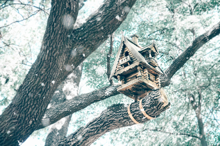Bird feeder, birdhouse in winter. Carved wooden rustic treehouse in the winter in the snow