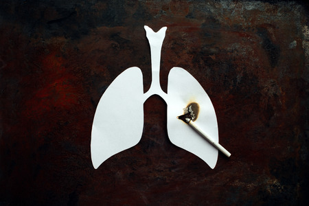 Stop Quit Smoking. Paper white lungs with burned hole and cigarette with smoke on dark rusty old background. Smoking kills, concept with cigarette and lungs. No smoking concept