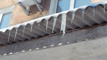 Big melting Icicles hang from roof of building. Danger for passers, threat of death and injury from icicles. Winter threats. Фото со стока