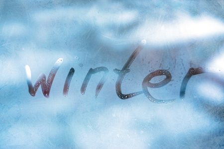 WINTER cold weather concept. Inscription word WINTER on the blue glass window with frozen patterns. Stock Photo