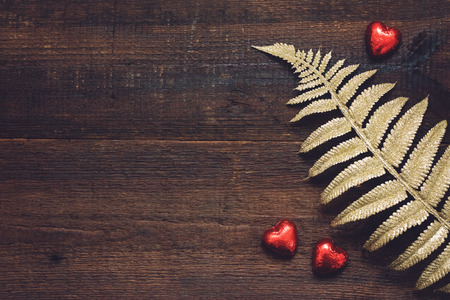 Valentines Day background, mockup with red heart shape chocolate candies and golden leaves on wooden background. Valentine Day, love, romance, dating concept, copy space Reklamní fotografie