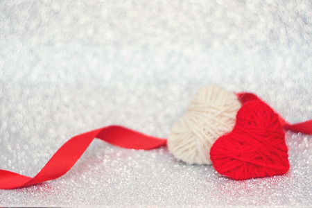 Valentines Day background, mockup with two red knitted fluffy heart on silver shiny glitter background. Valentine Day, love, romance, dating concept, copy space
