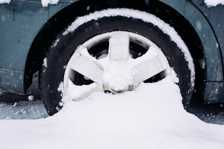 Car wheel with winter tires stalled in the snow. Wheel stuck in a snowdrift. Snow drifts on road, bad weather