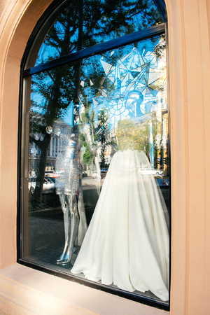 ODESSA, UKRAINE  – 22 September, 2018: Female mannequin in wedding dress in showcase. Bridal dresses Salon Showcase window display with reflections of the sky and buildings