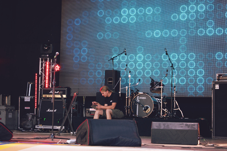 KROPIVNITSKIY; UKRAINE  – 16 September; 2017: Repetition of rock music band. Concert audio equipment tuning. A man tunes musical equipment on the stage before the concert