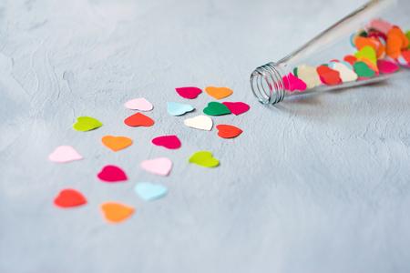 Créativité de la Saint-Valentin, cadeau de bricolage, idées de cartes. De nombreux coeurs en papier multicolore sont versés à partir d'une bouteille transparente en verre sur fond de ciment gris. Minimal, amour, romance, concept fait main