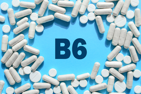 Vitamin B6 text in white capsules frame on blue background. Pill with Pyridoxine; Pyridoxal. Dietary supplements and medication