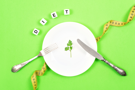 Diet, weigh loss, healthy eating, fitness concept. Small portion of food on big plate. Small green salad leaf on white plate with fork and knife and text diet on the background of measuring tape. Stock Photo