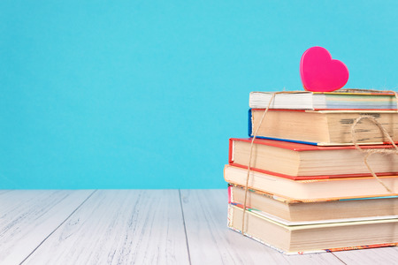 Stack of books and pink heart. Books with jute ribbon bow as gift on blue background. Education background with copy space, back to school concept. Stock Photo