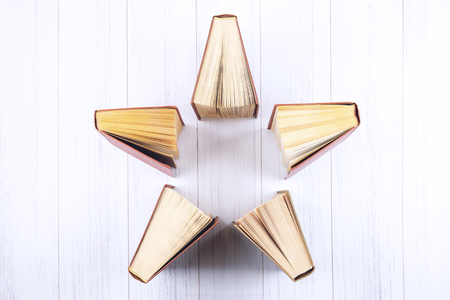 Book background. Top view of open hardback books in star shape on wooden table. Education, literature, knowledge, Back to school. Copy space.