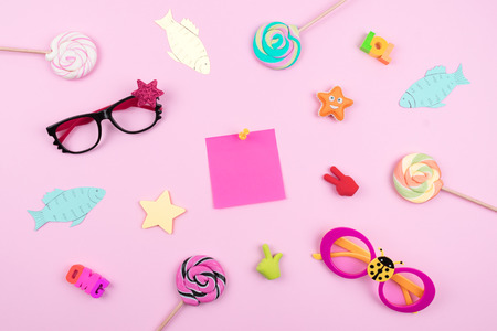 Festive funny celebration background with paper fish, sticky note and decor on pink background. All Fools Day, humor, prank, joke concept