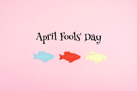 April Fools Day celebration background with paper fish and text on pink background. All Fools Day, humor, prank, joke concept.