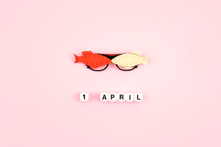 April Fools Day celebration. Glasses with paper fish and text 1 April on pink background. All Fools Day, humor, prank, joke concept.