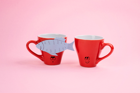 April Fools Day celebration, paper fish prank. Two joking laughing coffee cups with paper fish on pink background. All Fools Day, humor, prank, joke concept.