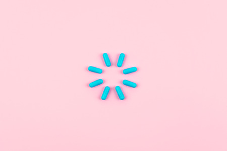 Bright blue pills in load symbol on pink background. Medicines, drugs, pharmacy concept. Flat lay, top view, minimal style.
