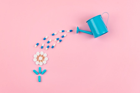 Bright blue and white pills and tablets in flower shape and garden watering can on pink background. Medicines, drugs, pharmacy concept. Flat lay, top view, minimal style.