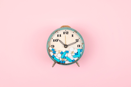 Old alarm clock with Tablets, medicine and pills on clock face on pink background. colorful capsules on  clock. Health care, reform, Take medicine on time concept.