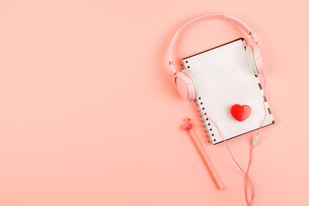 Minimal workplace with white blank notepad, pink headphones, heart, pencil on coral background. Top view. Flat lay. Stock Photo
