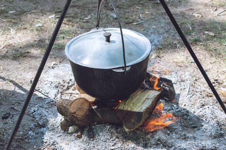 Hiking pot, Bowler in the bonfire. Fish soup boils in cauldron at the stake. Traveling, tourism, picnic cooking.