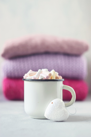 Coffee with marshmallows in white enameled metal cup and white heart on the background of stack of pink knitted sweaters on table.