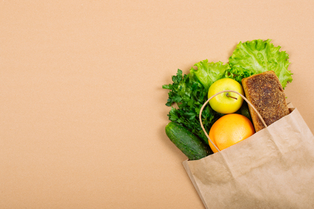 Diet, weigh loss, healthy eating, fresh food concept. Healthy food whole grain bread, vegetables, fruits and greens, herbs with paper bag on green background.