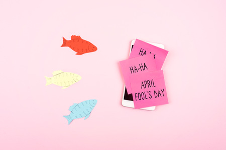 April Fools Day celebration background with paper fish, Smartphone and sticky note on pink background. All Fools Day, humor, prank, joke concept. Stock Photo