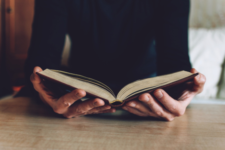 Man holding Open book in hands. Male hands hold a hardcover book. Education, literature, knowledge, reading concept. Copy space.