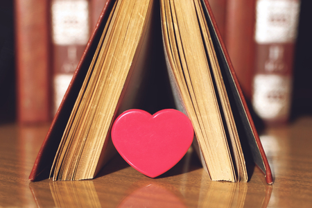 Open book with coral heart on the bookshelf background. Pink plastic Heart in the pages of the book.  Education, literature, knowledge, love background.