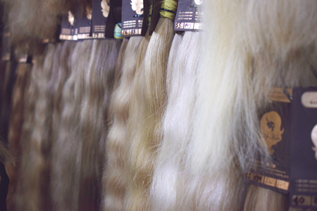 KIEV, UKRAINE – 19 SEPTEMBER, 2018: Clip-in Hair extensions  equipment of natural hair. Hair ombre Balayage samples of different colors. Multi-colored strands, bunches set for hair extension procedure