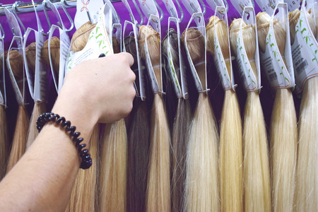 KIEV, UKRAINE – 19 SEPTEMBER, 2018: Women choose Clip-in Hair extensions equipment of natural hair. Hair ombre Balayage samples. Multi-colored strands, bunches set for hair extension. Editorial