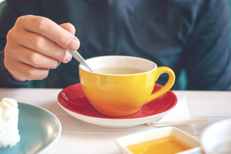 Mans hand with a spoon of honey over a yellow cup of tea. Tea time in cafe, Tea party Stock Photo
