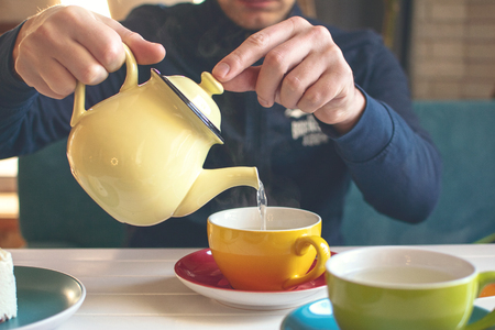 Mans hand with a yellow teapot pours herbal tea into a cup. Tea time in cafe, Tea party. Stock Photo
