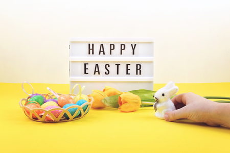 Easter composition, greeting card with child hand, toy bunny, lightbox text Happy Easter, colored decorative eggs, yellow tulips on color background