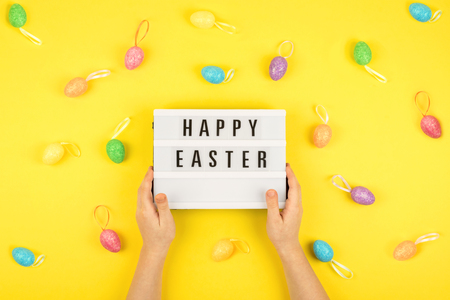 Easter composition, greeting card with child hand, lightbox text Happy Easter, colored decorative eggs on color background