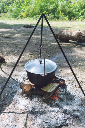Hiking pot, Bowler in the bonfire. Fish soup boils in cauldron at the stake. Traveling, tourism, picnic cooking