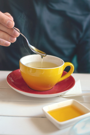 Mans hand with a spoon of honey over a yellow cup of tea. Stock Photo