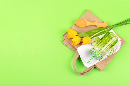 Zero waste living concept. Zero waste no plastic kit, Reusable Bag, Mason Jar, Microfiber Cloth, craft paper bag and yellow tulips on green background. Stock Photo