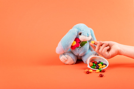 Child hand feeds the Easter rabbit sweet multicolored dragee on coral background. Decorative Easter festive composition, greeting card