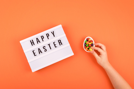 Easter composition, greeting card with child hand, lightbox text Happy Easter, yellow tulips, chocolate eggs with multicolored dragee on color background
