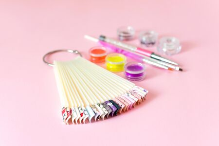 Manicure, gel nail art design equipment, tools and samples on pink background
