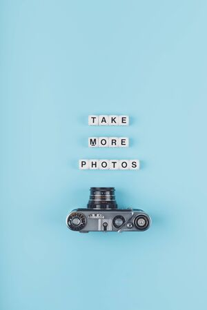 Take more photos text from white cubes and the old film camera in the background on a blue background. Photography School, classes, course, workshop concept