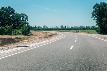 New asphalt road with roadside construction site in the forest. Countryside asphalt road reconstruction Imagens